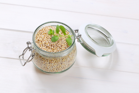 jar of pearl barley on white wooden background