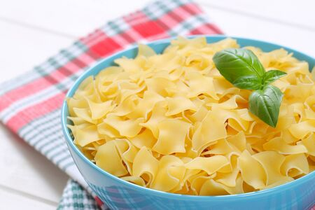 bowl of quadretti - square shaped pasta on checkered place mat - close up Stock Photo