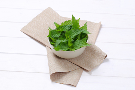 bowl of fresh nettle leaves on beige place mat