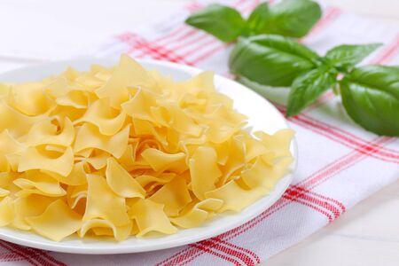 plate of quadretti - square shaped pasta on checkered dishtowel - close up Stock Photo