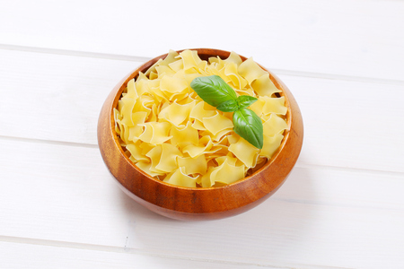 bowl of quadretti - square shaped pasta on white wooden background