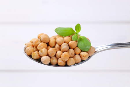 spoon of raw chickpeas on white wooden background Stock Photo