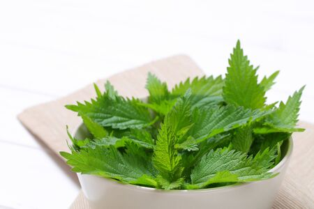 bowl of fresh nettle leaves on beige place mat - close up