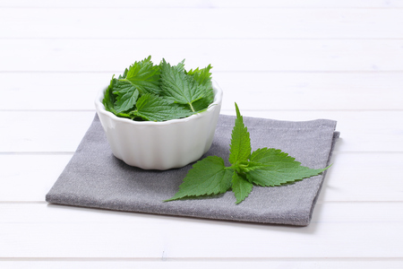 bowl of fresh nettle leaves on grey place mat