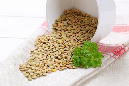 bowl of dry brown lentils spilt out on white dishtowel - close up Stock Photo