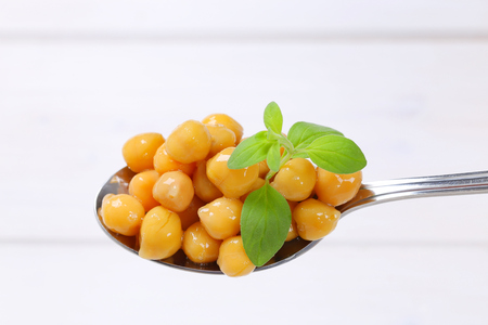 spoon of cooked chickpeas on white wooden background Stock Photo