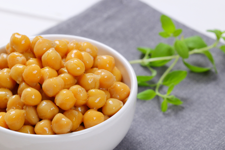 bowl of cooked chickpeas on grey place mat - close up Standard-Bild
