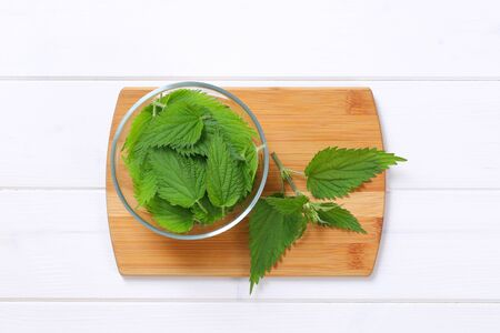 bowl of fresh nettle leaves on wooden cutting board Stock Photo
