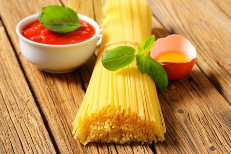 Bundle of dried spaghetti, tomato passata and egg on wooden background Reklamní fotografie