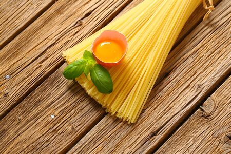 Dried spaghetti and raw egg on wooden background