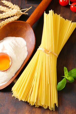 Bundle of dried spaghetti, scoop of flour and fresh egg Reklamní fotografie