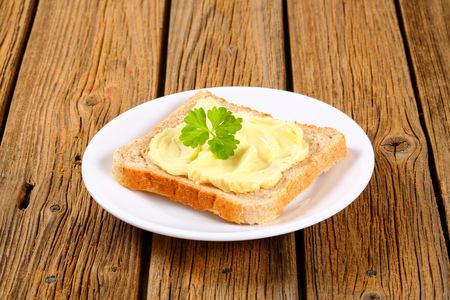 Slice of toast bread with butter on a plate