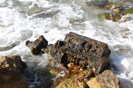 Rusty piece of iron washed up on the sea shore Reklamní fotografie