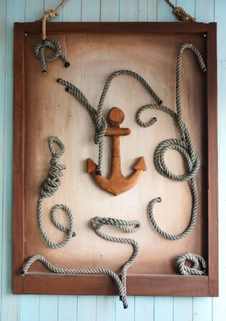 Framed wooden anchor and knots as decoration on wall Reklamní fotografie