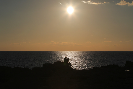 Silhouettes of two people sitting on rock on seashore at sunset