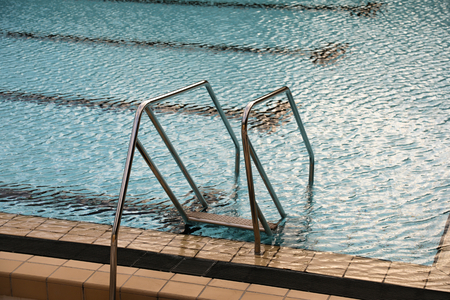 Steel stairs with handrails into the swimming pool
