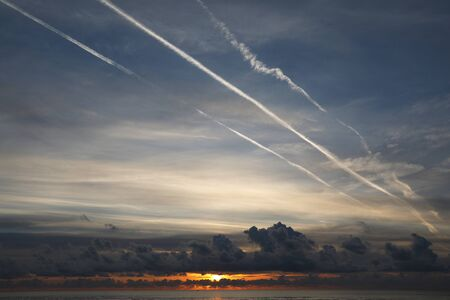 View of the sunset over the sea with dark clouds and white lines in the sky