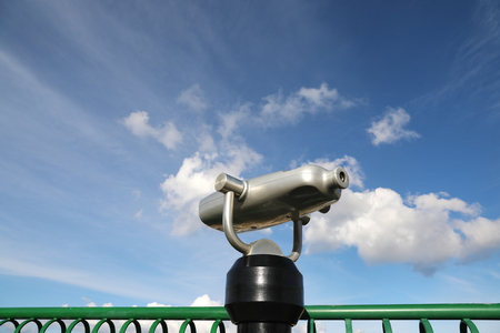 Coin-operated spy viewing machine against cloudy sky