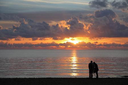 바다에 일몰의 사진을 찍고 해변에서 두 정체 불명의 사람들의 실루엣