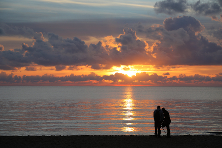 Silhouettes of two unidentifiable people on the beach taking photos of sunset over the sea