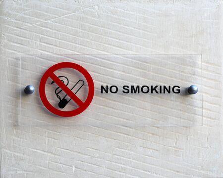 No smoking notice on white wall Reklamní fotografie