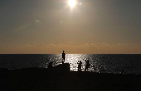 해변에서 일몰을 즐기는 4 명의 사람들의 실루엣