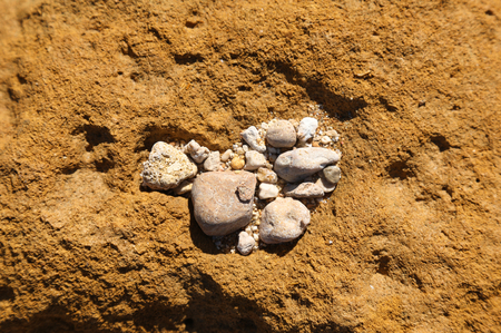 Group of small stones on brown rock