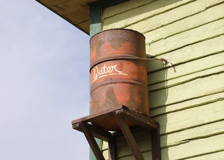 Old rusty rainwater barrel attached to house, Popeye village, Malta
