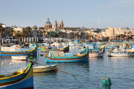 Traditional colorful fishing boats Luzzu moored at Marsaxlokk (Marsascala) Harbor, Malta Redakční