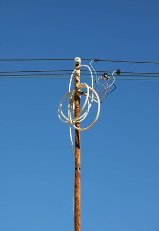 Tangled wires on rusty power pole against blue sky