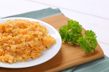 side shot: Plate of cooked red lentils on cutting board Stock Photo