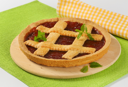 strawberry jam tart with lattice on wooden cutting board