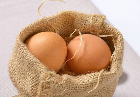 burlap sack of brown eggs and straw - close up Reklamní fotografie