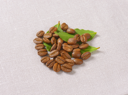 handful of roasted coffee beans with leaves on linen napkin