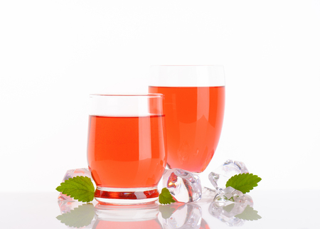 two glasses of strawberry juice on white background