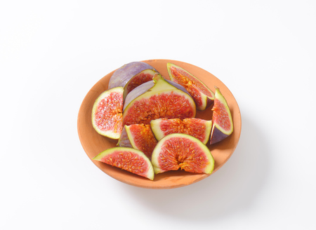 bowl of fresh sliced figs on white background