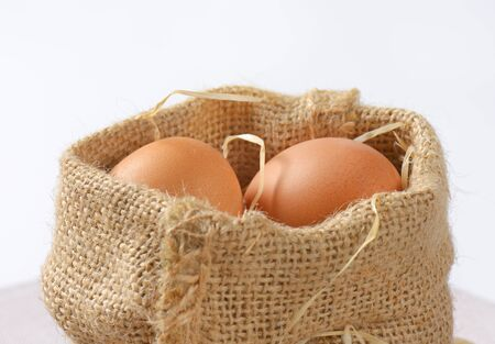 burlap sack of brown eggs and straw