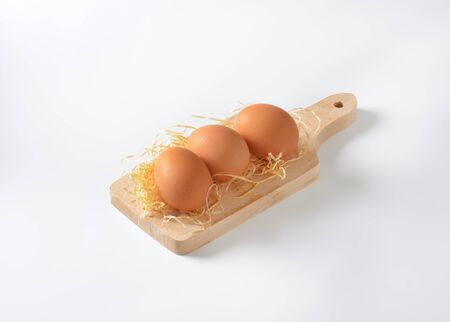 brown eggs and straw on wooden cutting board Reklamní fotografie