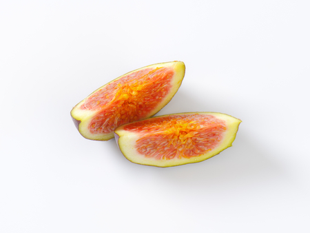 two slices of ripe fig on white background