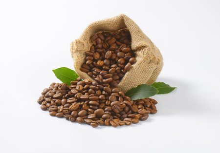 burlap sack full of coffee beans on white background
