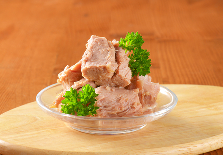 bowl of canned tuna with parsley on wooden cutting board - close up Reklamní fotografie