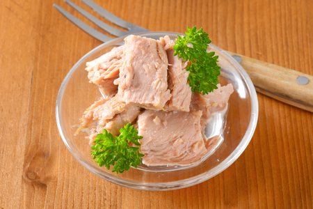 bowl of canned tuna with parsley on wooden table Reklamní fotografie