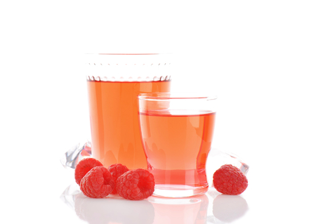 glasses of raspberry juice and fresh raspberries on white background
