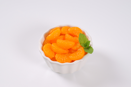 bowl of canned tangerine segments on white background