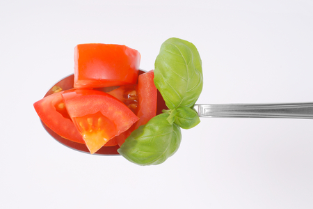 spoon of sliced tomato and basil on white background Stock Photo - 87772849
