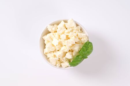 bowl of crumbled white cheese on white background Stock fotó