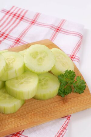pile of sliced cucumber on wooden cutting board Stock Photo