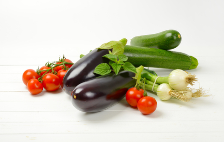 fresh eggplants, tomatoes, zucchini and spring onion on white wooden background
