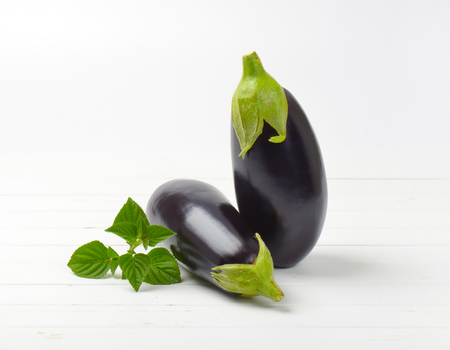 two fresh eggplants and sage on white wooden background Stock Photo