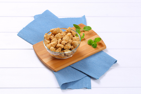 bowl of soy meat cubes on wooden cutting board